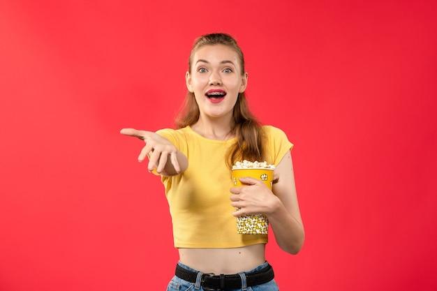 Giovane femmina di vista frontale al cinema che tiene il pacchetto del popcorn sulla ragazza del film del cinema del cinema di film della parete rossa chiaro