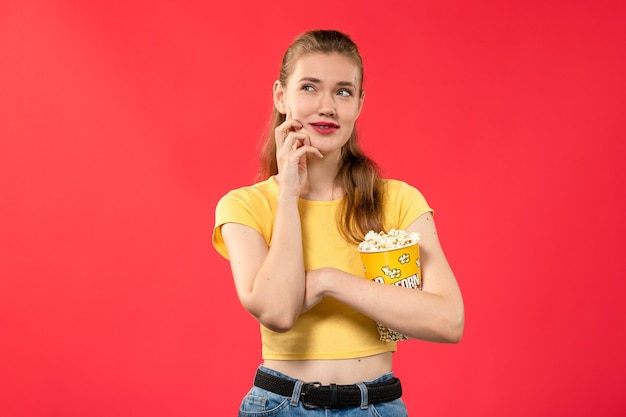 Front view young female at cinema holding popcorn package on light red wall theater movies cinema film