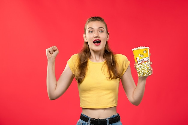 Giovane femmina di vista frontale al cinema che tiene il pacchetto del popcorn e che si rallegra sul film di divertimento femminile del cinema del cinema di film della parete rossa