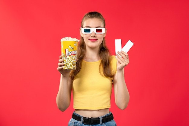 Front view young female at cinema holding popcorn package and tickets on light-red wall theater movies cinema film