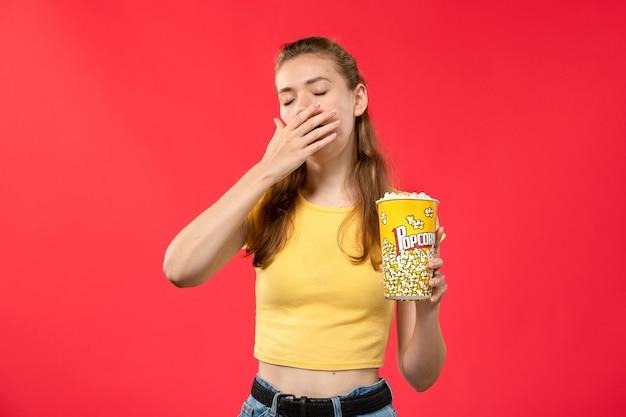 Giovane femmina di vista frontale al cinema che tiene il pacchetto del popcorn e che sbadiglia sul film di divertimento femminile del cinema del cinema di film della parete rossa