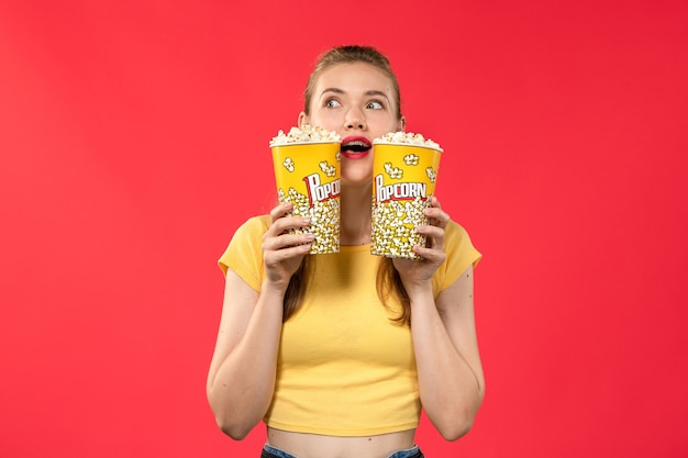 Front view young female at cinema holding popcorn packages on red wall movie theater cinema snack female fun film