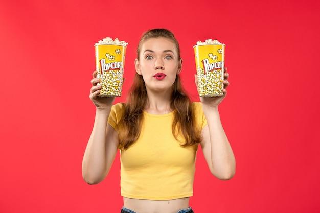 Giovane femmina di vista frontale al cinema che tiene i pacchetti del popcorn sul film di divertimento femminile dello spuntino del cinema del teatro dei film della parete rossa