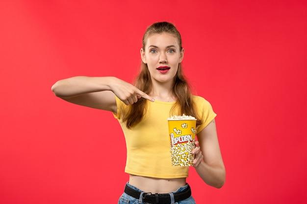 Giovane femmina di vista frontale al cinema che tiene popcorn e che posa sul film di divertimento femminile dello spuntino del cinema del cinema della parete rossa dei film