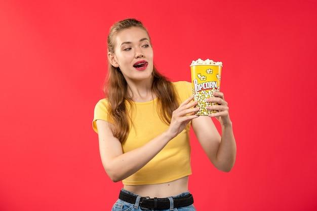Giovane femmina di vista frontale al cinema che tiene popcorn sul colore femminile del cinema del cinema del cinema della parete rossa