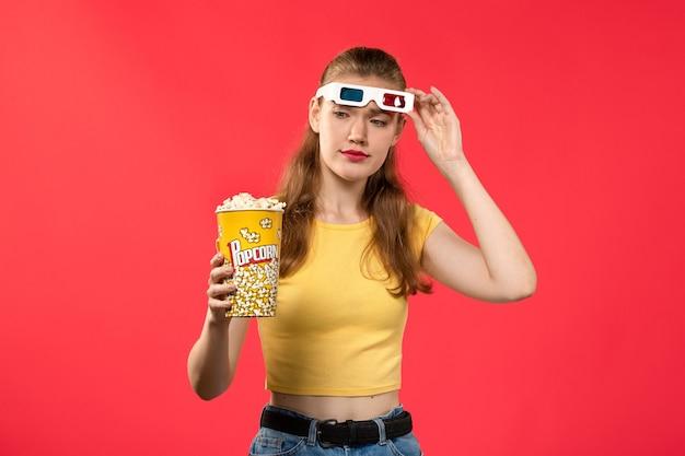 Giovane femmina di vista frontale al cinema che tiene popcorn sul colore femminile del cinema del teatro di film della parete rossa