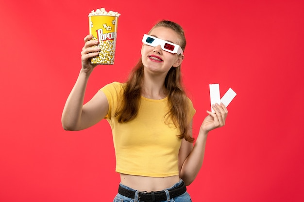 Front view young female at cinema holding popcorn and tickets in d sunglasses on the red wall movie theater cinema female colors