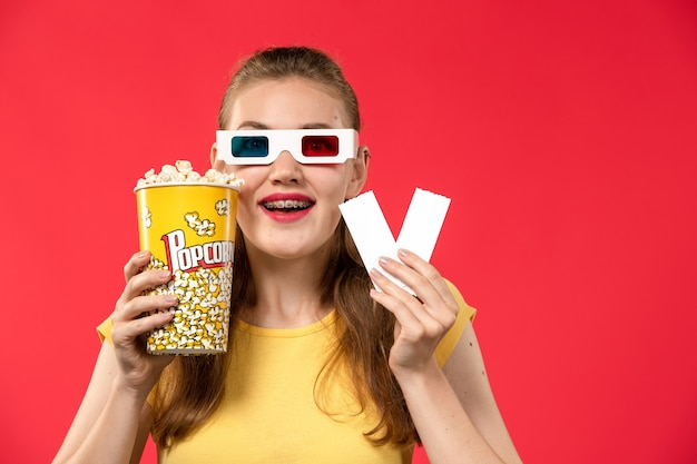 Front view young female at cinema holding popcorn and tickets on red wall movie theater cinema female colors