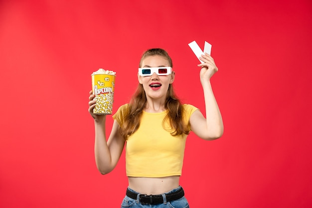 Front view young female at cinema holding popcorn and tickets on the red wall movie theater cinema female colors