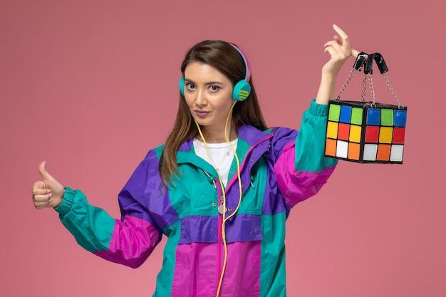 Giovane femmina di vista frontale in auricolari moderni variopinti del cappotto che tengono la borsa sulla parete rosa, vestiti di modo della donna della foto a colori