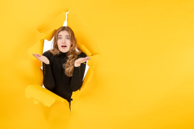 Вид спереди молодая женщина смущена на желтой разорванной стене
