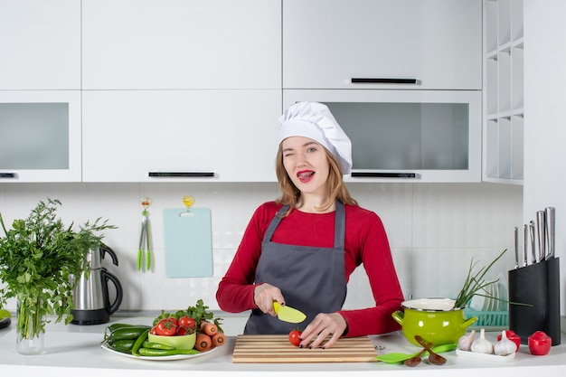 Vista frontale giovane cuoca in grembiule con pomodoro a pezzi con occhi sbattuti dalle palpebre