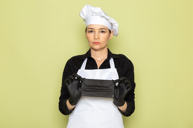 A front view young female cook in black shirt white cook cape white cap posing in black gloves holding black mask posing