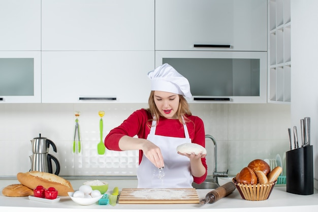 Front view young female cook in cook hat and apron holding dough and sprinkling flour to cutting board in the kitchen