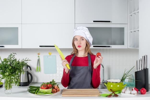 トマトを持ち上げてエプロンで若い女性料理人の正面図