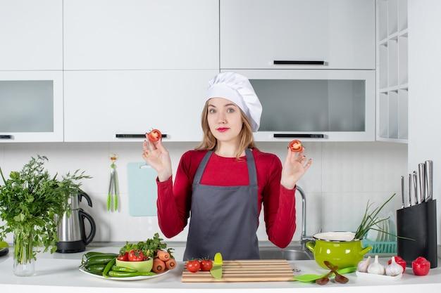 Вид спереди молодая женщина-повар в фартуке, подняв помидоры