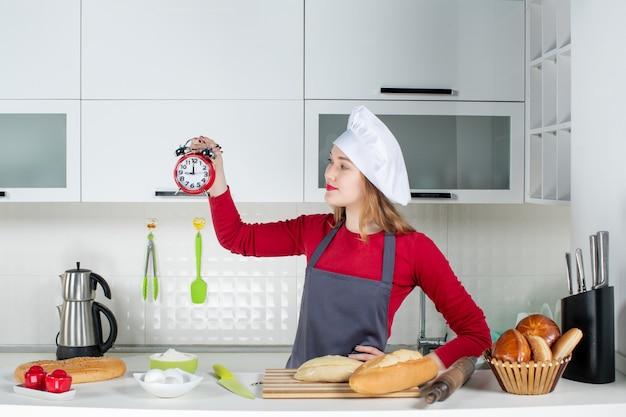 Вид спереди молодая женщина-повар в поварской шляпе и фартуке держит красный будильник на кухне