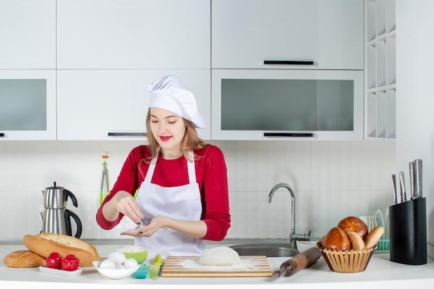正面図キッチンのボウルから小麦粉を取るクック帽子とエプロンで若い女性料理人