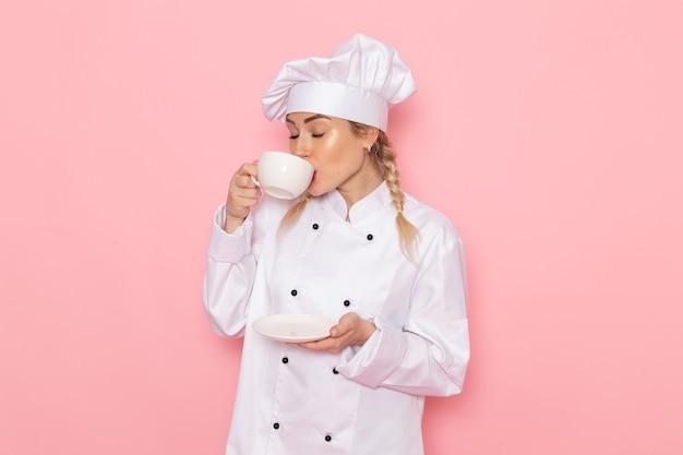 Вид спереди молодая женщина-повар в белом костюме повара пьет горячий кофе на розовом космическом поваре