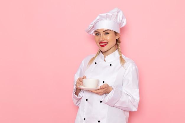 ピンクのスペースクックに笑顔で一杯のコーヒーを保持している白いクックスーツで正面の若い女性クック