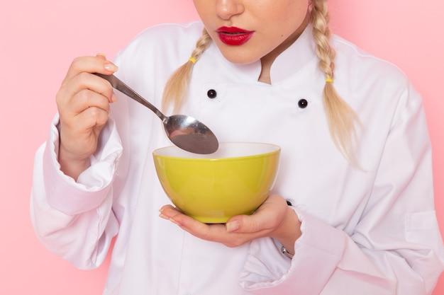 ピンクのスペースクックでそれを味わうグリーンプレートを保持している白いクックスーツで正面の若い女性クック