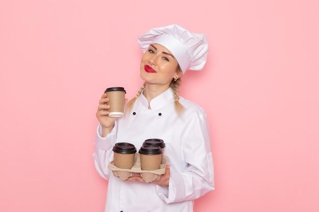 ピンクのスペースクック料理写真にプラスチック製のコーヒーカップを保持している白いクックスーツで正面の若い女性クック