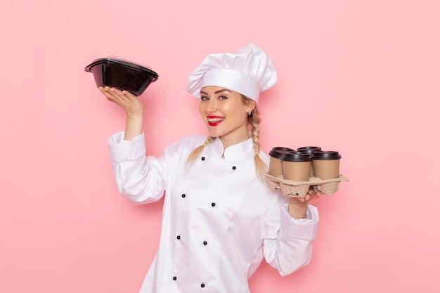 Вид спереди молодая женщина-повар в белом костюме повара держит пластиковые кофейные чашки с миской для еды на розовом космическом поваре