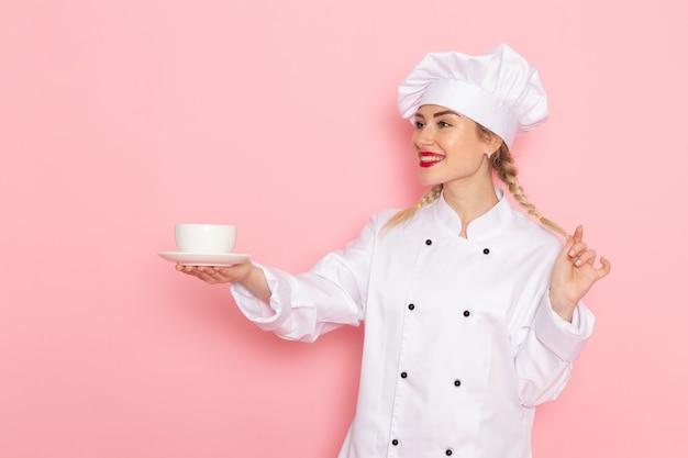 Вид спереди молодая женщина-повар в белом костюме повара держит белую чашку с кофе на розовом космическом поваре