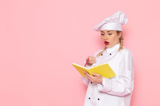 Вид спереди молодая женщина-повар в белом костюме повара с желтой тетрадью и карандашом на розовом пространстве готовит еду