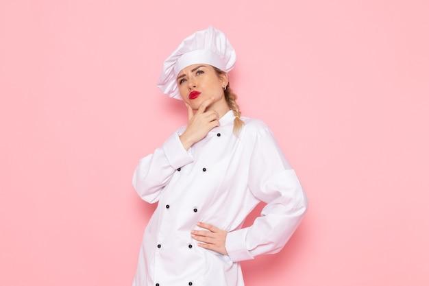 Вид спереди молодая женщина-повар в белом костюме повара позирует с выражением мышления на розовом пространстве, повар кухня работа работа фото