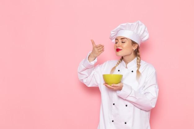 ピンクのスペースクック料理仕事の仕事の写真に食べ物の臭いがする白いスーツで正面の若い女性クック