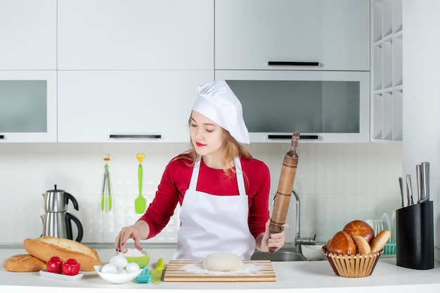 Front view young female cook sprinkling flour to dough on cutting board holding rolling pin in the kitchen