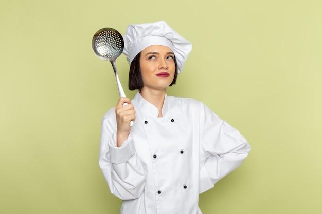 Un giovane cuoco femminile di vista frontale in vestito bianco del cuoco e cucchiaio della tenuta del cappuccio con l'espressione di pensiero sul colore di cucina dell'alimento del lavoro della signora della parete verde