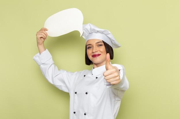 Una giovane cuoca femminile di vista frontale in vestito bianco e cappuccio del cuoco che tiene segno bianco sul colore verde della cucina dell'alimento della signora del lavoro della parete