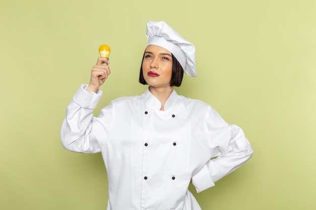 A front view young female cook in white cook suit and cap holding yellow lightbulb on the green wall lady work food cuisine color