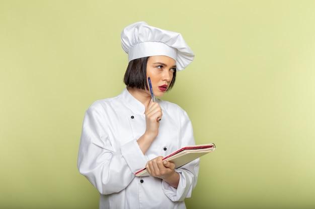Una giovane cuoca femminile di vista frontale in vestito bianco e cappuccio del cuoco che posa pensando e annotando sul colore della cucina dell'alimento del lavoro della signora della parete verde