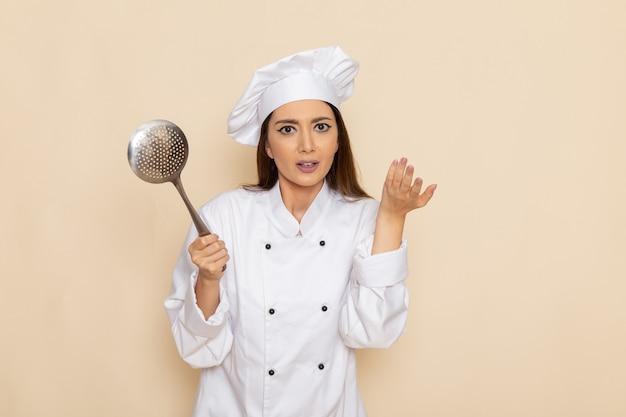 Vista frontale del giovane cuoco femminile in vestito bianco del cuoco che tiene grande cucchiaio d'argento sulla parete bianca