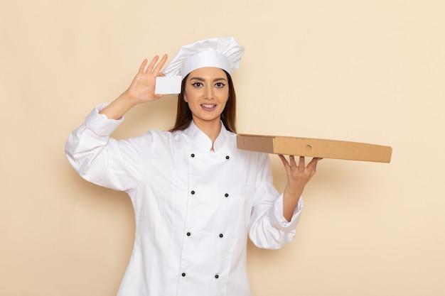 Vista frontale del giovane cuoco femminile in vestito bianco da cuoco che tiene carta e scatola di cibo sul muro bianco