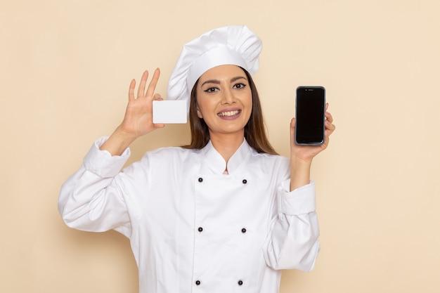 Vista frontale del giovane cuoco femminile in carta bianca della tenuta del vestito del cuoco e telefono sul muro bianco-chiaro