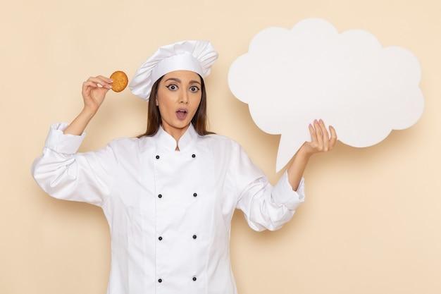 Vista frontale della giovane cuoca in vestito bianco da cuoco che tiene il biscotto sulla parete bianco-chiaro