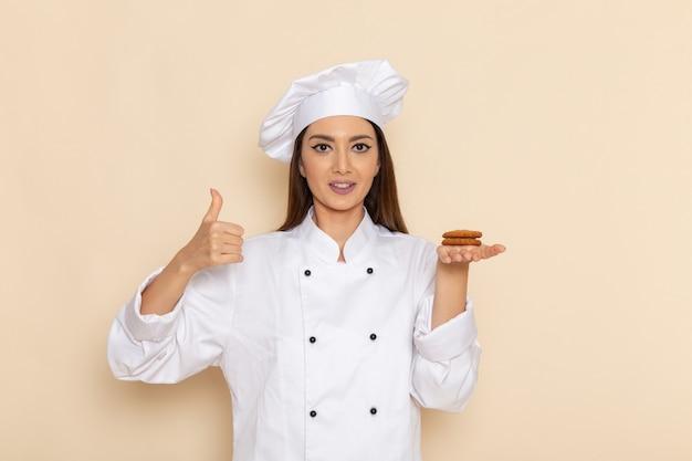 Vista frontale della giovane cuoca in vestito bianco da cuoco che tiene i biscotti sulla parete bianca leggera
