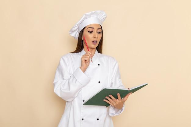 Vista frontale della giovane cuoca in vestito bianco da cuoco che tiene il quaderno e pensa sulla parete bianco-chiaro