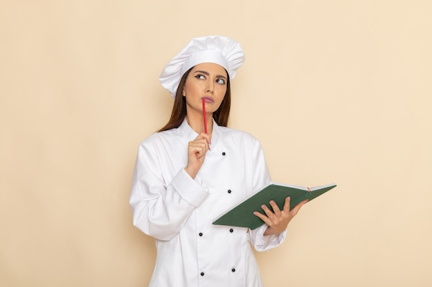 Front view of young female cook in white cook suit holding copybook and thinking on light-white wall