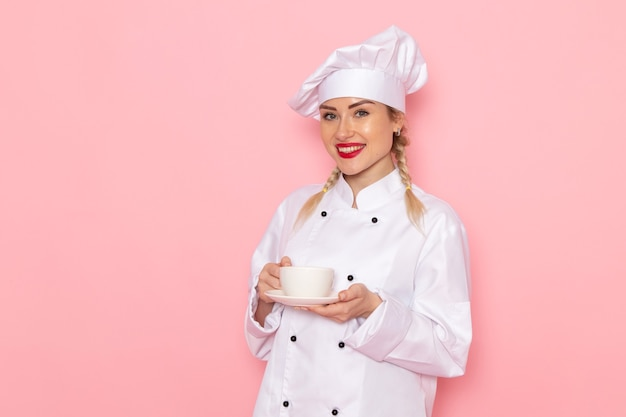 Front view young female cook in white cook suit holding cup of coffee with smile on the pink space cook