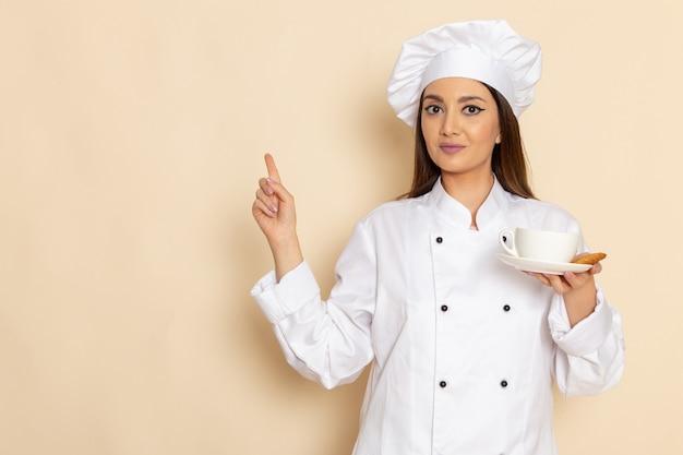 Vista frontale di giovane cuoco femminile in vestito bianco cuoco che tiene tazza con caffè sulla parete bianca