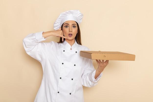 Vista frontale della giovane cuoca in vestito bianco da cuoco che tiene la scatola di cibo sul muro bianco-chiaro