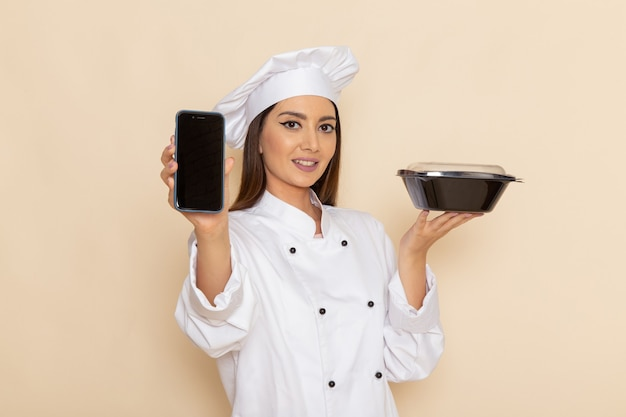 Front view of young female cook in white cook suit holding phone and black bowl on the white wall