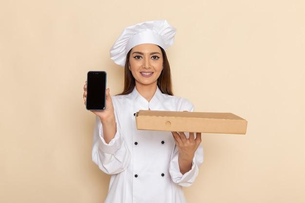 Vista frontale della giovane donna cuoca in vestito bianco da cuoco che tiene il telefono e la scatola di cibo sulla parete bianco-chiaro
