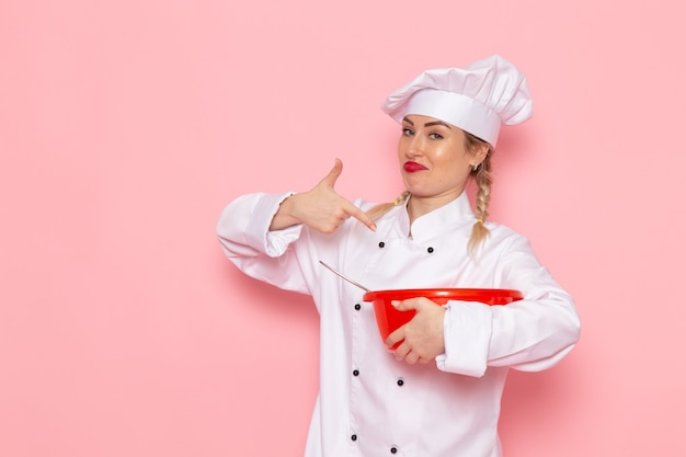 Front view young female cook in white cook suit holding red plastic bowl on the pink space cook  food meal