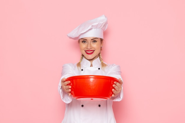 Front view young female cook in white cook suit holding red plastic bowl on the pink space cook